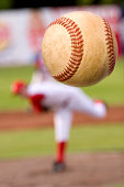 A baseball player pitching with spin on the ball. (motion blur on ball)