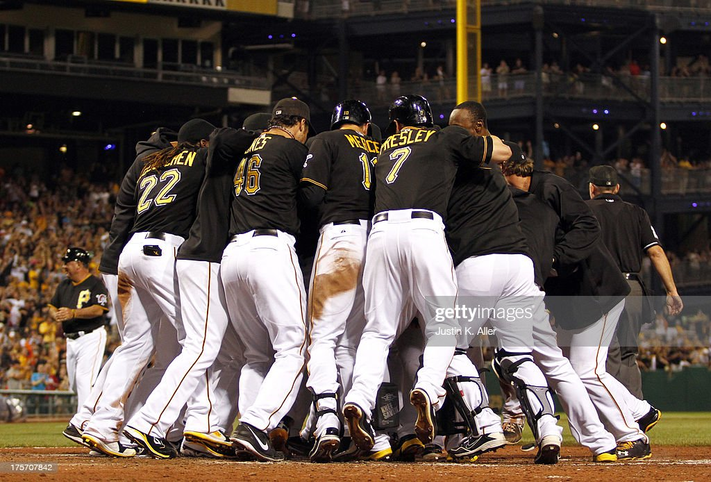 The Pittsburgh Pirates celebrate with Josh Harrison #5 after hitting a ninth inning walk off home run against the Miami Marlins on August 6, 2013 at PNC Park in Pittsburgh, Pennsylvania. The Pirates defeated the Marlins 4-3.