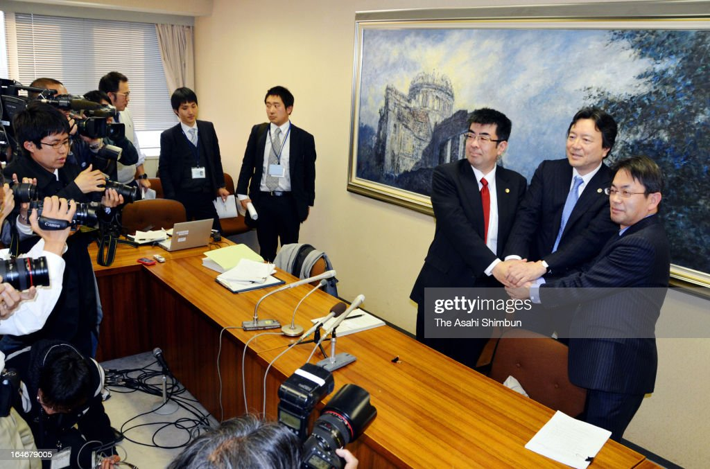 The plaintiff lawyer group shake hands during a press conference on March 25, 2013 in Hiroshima, Japan. In a landmark decision, the Hiroshima High Court ruled on March 25 that the results of the Dec. 16 Lower House election in two constituencies were invalid due to the wide gap in the value of votes.