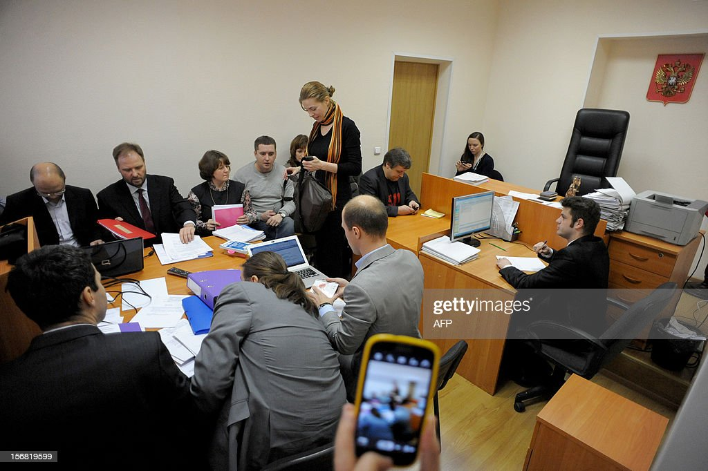 The plaintiffs (back) and the respondents (front) for a suit against US pop star Madonna sit at the table in a courtroom in St.Petersburg, on November 22, 2012. A court in St.Petersburg started today to hear a $10.5 million suit brought against Madonna by Russian nationalists who claim she violated local law by promoting gay rights during her summer concert in the Russia's second city.