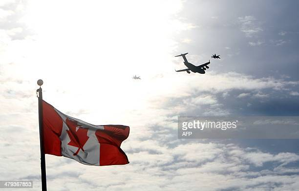 The plane carrying the last of Canada's troops in Afghanistan is escorted through the air by fighter jets after the last Canadian troops from...