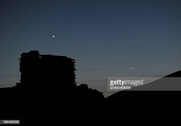 The planets Jupiter Venus and Mercury are seen in an unusual conjunction setting over the Wupatki pueblo ruin on May 24 2013 at Wupatki National...