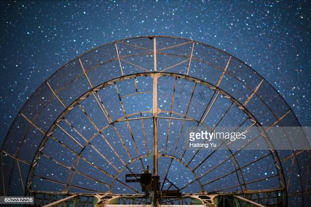 The plate of a radio telescope antenna under starry sky