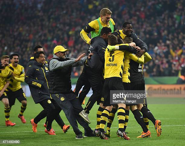 The players and head coach Juergen Klopp celebrate after winning during the penalty shoot out during the DFB Cup semi final match between FC Bayern...