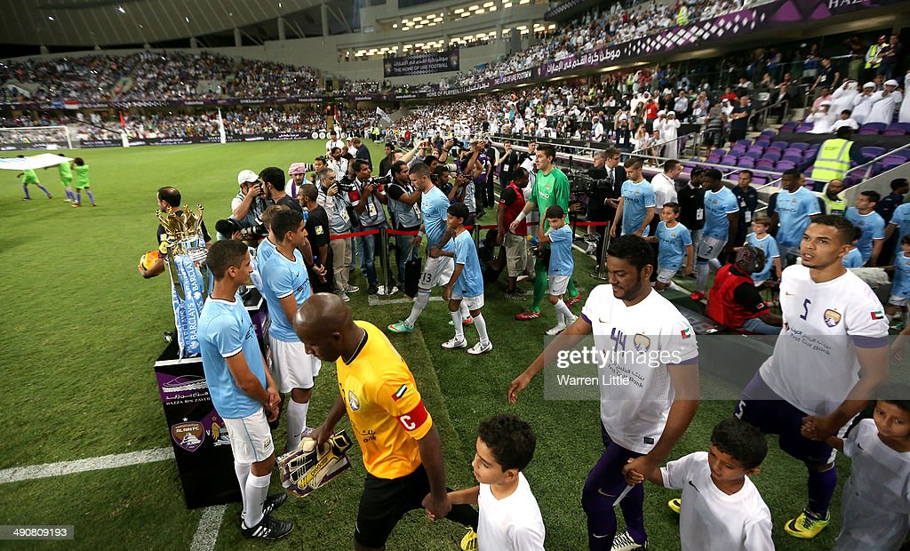 The players enter the pitch passing the Premier League trophy during the friendly match between Al Ain and Manchester City at Hazza bin Zayed Stadium on May 15, 2014 in Al Ain, United Arab Emirates.