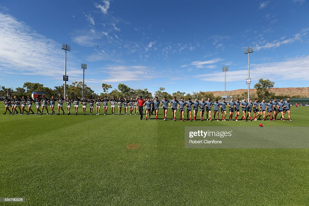The players from both teams link arms to show their support againsts family violence prior to the round 10 AFL match between the Melbourne Demons and the Port Adelaide Power at Traeger Park on May 28, 2016 in Alice Springs, Australia.