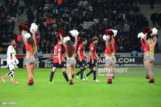 The players leave the pitch at half time under the watchful gaze of the pom pom girls during the French Ligue 1 match between Lille OSC and OGC Nice...