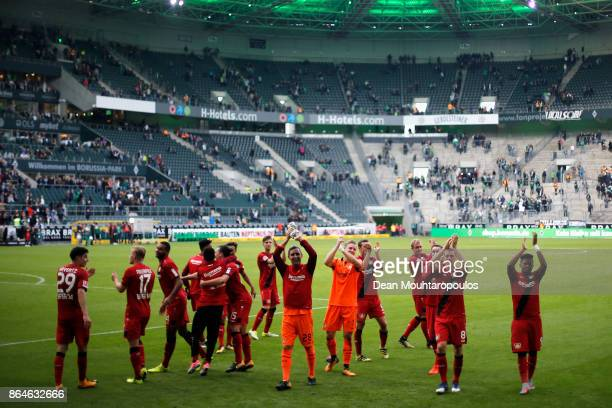 The players of Bayer 04 Leverkusen celebrate in front of their fans after victory in the Bundesliga match between Borussia Moenchengladbach and Bayer...