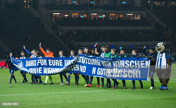 The players of Berlin hold a banner featuring a thank you and best wishes for Christmas after the end of the Bandesliga match between Hertha BSC and...