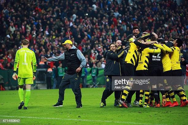 The players of Dortmund celebrate as head coach Juergen Klopp trys to shake hands with Manuel Neuer of Muenchen after winning during the penalty...