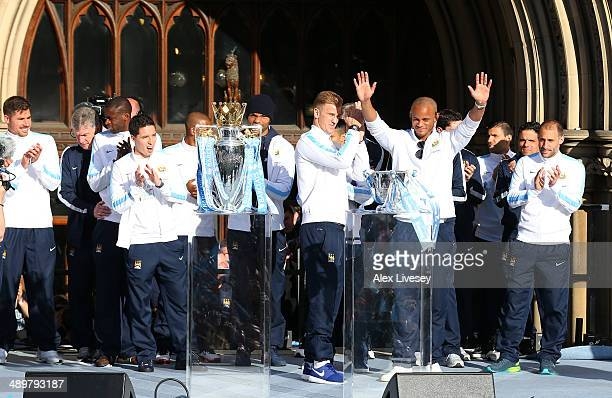 The players of Manchester City salute their supporters outside Manchester Town Hall at the start of the Manchester City victory parade around the...