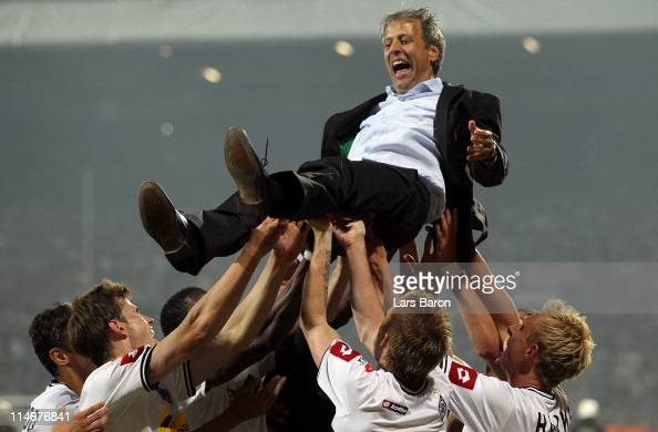 The players of Moenchengladbach throw head coach Lucien Favre up in the air after the Bundesliga play off second leg match between VfL Bochum and...