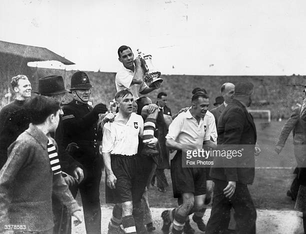 The players of Preston North End carry the trophy aloft after their 10 extra time victory over Huddersfield Town in the FA Cup final at Wembley Bill...