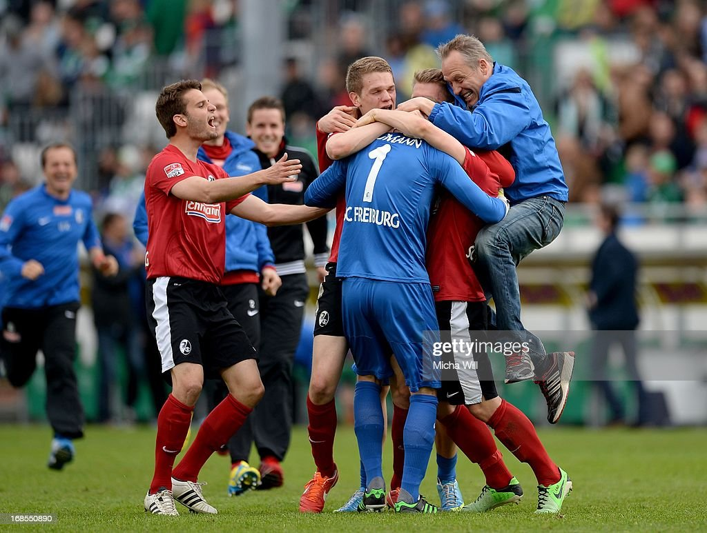 The players of SC Freiburg and head coach <a gi-track='captionPersonalityLinkClicked' href=/galleries/search?phrase=Christian+Streich&family=editorial&specificpeople=4411796 ng-click='$event.stopPropagation()'>Christian Streich</a> (R) celebrate their win with goalkeeper Oliver Baumann of Freiburg who hold a penalty during the Bundesliga match between SpVgg Greuther Fuerth and SC Freiburg at Trolli-Arena on May 11, 2013 in Fuerth, Germany.