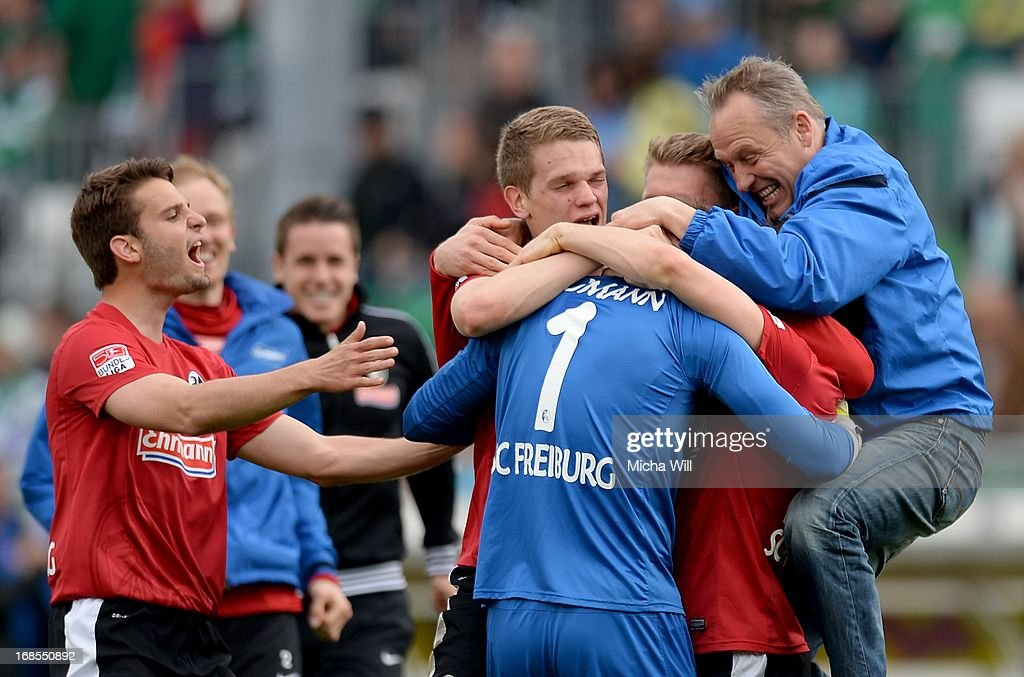 The players of SC Freiburg including their head coach <a gi-track='captionPersonalityLinkClicked' href=/galleries/search?phrase=Christian+Streich&family=editorial&specificpeople=4411796 ng-click='$event.stopPropagation()'>Christian Streich</a> (R) celebrate their win around goalkeeper Oliver Baumann of Freiburg who hold a penalty during the Bundesliga match between SpVgg Greuther Fuerth and SC Freiburg at Trolli-Arena on May 11, 2013 in Fuerth, Germany.
