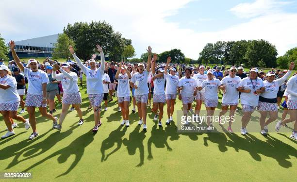 The players of Team USA walk down the 18th fairway linked arm in arm after the final day singles matches of The Solheim Cup at Des Moines Golf and...