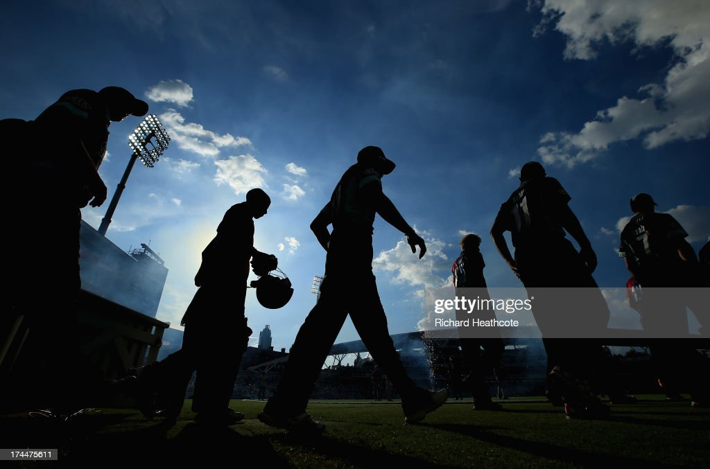 The players walk out to start the match during the Friends Life T20 match between Surrey Lions and Kent Spitfires at The Kia Oval on July 26 2013 in...