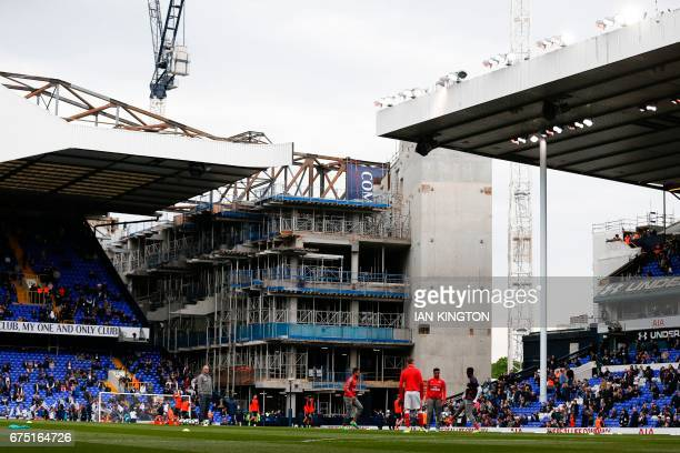 The players warm up with the building works for Tottenham's new stadium in the background ahead of the English Premier League football match between...