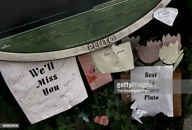 The Pluto Planet marker has several notes and cards attached and near to mourn it's loss as a fullfledged planet