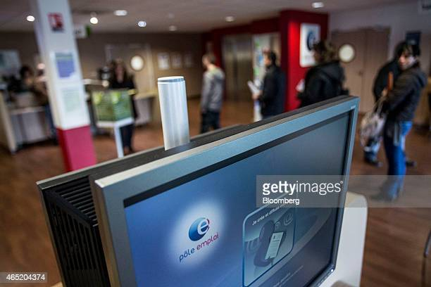 The Pole Emploi logo sits on a computer monitor as jobseekers queue at service desks inside a French national employment agency in Montauban France...