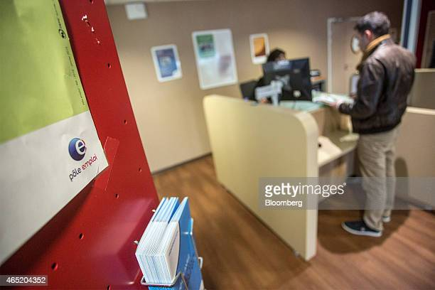 The Pole Emploi logo sits on display as a jobseeker stands at a service desks inside a French national employment agency in Montauban France on...