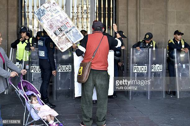 The police stand guard as demonstrators protest against the rise in fuel prices in Mexico City on January 7 2017 Violent demonstrations and looting...