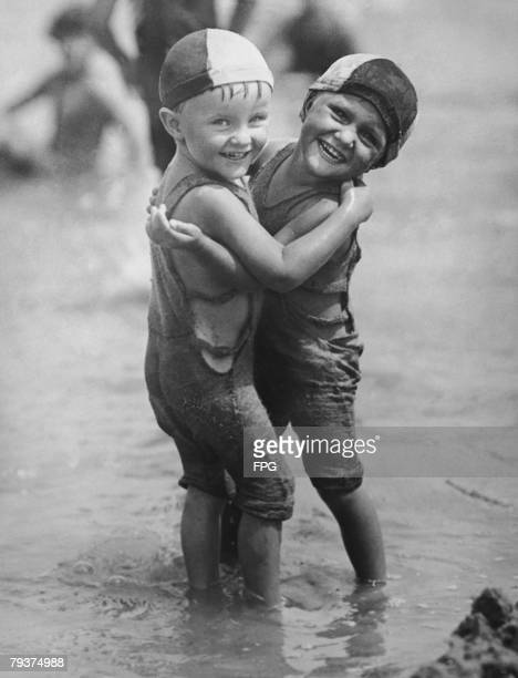 The Pomroy twins a boy and a girl mess about in the water in Boston circa 1930