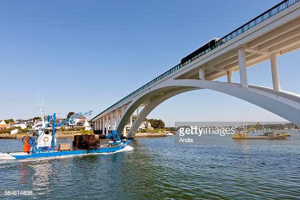 The 'pont de Kerisper' bridge over the Crac'h river which connects Saint Philibert with La Trinite sur Mer oyster boat under the bridge
