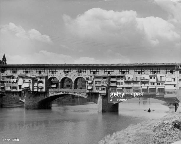 The Ponte Vecchio a Medieval stone arch bridge over the Arno River in Florence Italy circa 19201960