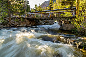 A Spring evening view of rapid Big Thompson River rushing down under a wooden bridge at The Pool of Fern Lake Trail. Rocky Mountain National Park, Colorado, USA.