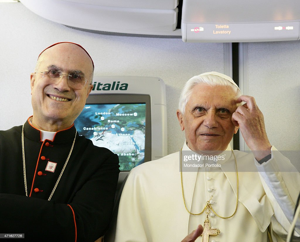 The pope Benedict XVI (Joseph Aloisius Ratzinger) with Italian cardinal <a gi-track='captionPersonalityLinkClicked' href=/galleries/search?phrase=Tarcisio+Bertone&family=editorial&specificpeople=549351 ng-click='$event.stopPropagation()'>Tarcisio Bertone</a> answering to the journalists on the airplane leading him to Brazil for the fifth Generale Conference of Latin American and Caribbean Episcopacy. May 2007