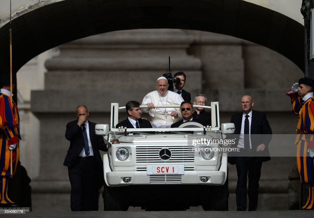 The popemobile is surrounded by bodyguards as Pope Francis arrives for his weekly general audience at St Peter's square on May 25, 2016 in Vatican. / AFP / Filippo MONTEFORTE