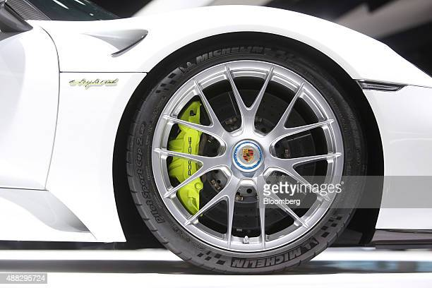The Porsche badge sits on a wheel hub of a Porsche AG 918 Spyder ehybrid automobile produced by Volkswagen AG sits on display during previews for the...