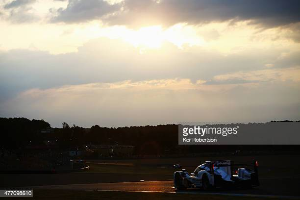 The Porsche Team 919 Hybrid of Earl Bamber Nick Tandy and Nico Hulkenburg drives at sunrise during the Le Mans 24 Hour race at the Circuit de la...