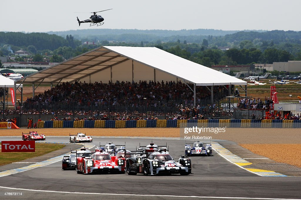 The Porsche Team 919 Hybrid (black right) of <a gi-track='captionPersonalityLinkClicked' href=/galleries/search?phrase=Romain+Dumas&family=editorial&specificpeople=805197 ng-click='$event.stopPropagation()'>Romain Dumas</a>, <a gi-track='captionPersonalityLinkClicked' href=/galleries/search?phrase=Neel+Jani&family=editorial&specificpeople=541892 ng-click='$event.stopPropagation()'>Neel Jani</a> and <a gi-track='captionPersonalityLinkClicked' href=/galleries/search?phrase=Marc+Lieb&family=editorial&specificpeople=3199675 ng-click='$event.stopPropagation()'>Marc Lieb</a> leads from its sister car, the Porsche Team 919 Hybrid (red left) driven by <a gi-track='captionPersonalityLinkClicked' href=/galleries/search?phrase=Mark+Webber+-+Piloto+de+automobilismo&family=editorial&specificpeople=167271 ng-click='$event.stopPropagation()'>Mark Webber</a>, <a gi-track='captionPersonalityLinkClicked' href=/galleries/search?phrase=Brendon+Hartley&family=editorial&specificpeople=4823179 ng-click='$event.stopPropagation()'>Brendon Hartley</a> and <a gi-track='captionPersonalityLinkClicked' href=/galleries/search?phrase=Timo+Bernhard&family=editorial&specificpeople=4194103 ng-click='$event.stopPropagation()'>Timo Bernhard</a> at the start of the Le Mans 24 Hour race at the Circuit de la Sarthe on June 13, 2015 in Le Mans, France.