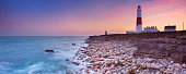 The Portland Bill Lighthouse on the Isle of Portland in Dorset, England at sunset.