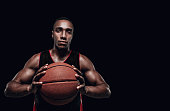 The portrait of a basketball player with a ball against dark studio background. advertising concept