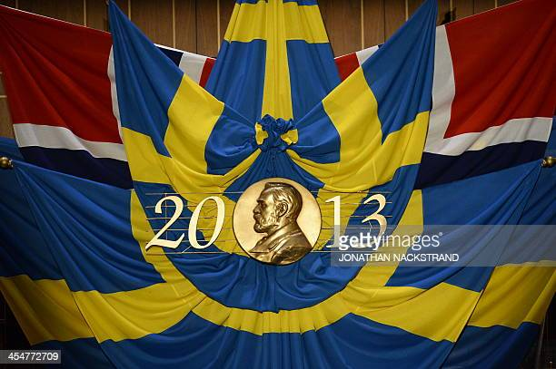 The portrait of Alfred Nobel can be seen in front of the national flags of Sweden and Norway prior to the Nobel Prize award ceremonies for Medicine...