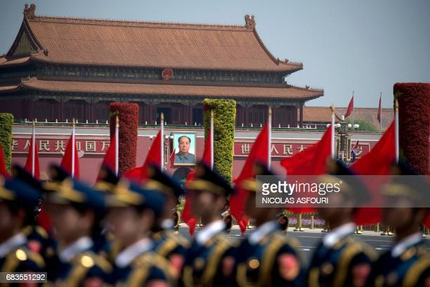 The portrait of late communist leader Mao Zedong is seen behind a Chinese military honour guard as they wait for the start of a welcome ceremony for...