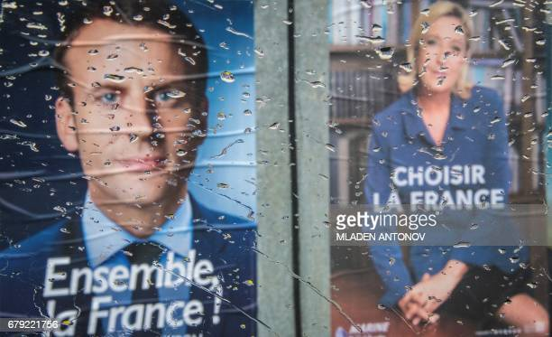 The posters of second round French Presidential elections candidates for the farright Front National party Marine Le Pen and for the En Marche...