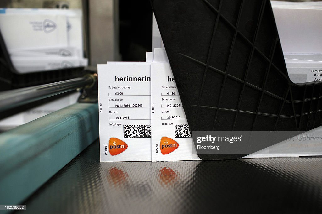 The PostNL logo is seen on postage payment shortfall notification letters as they sit in an envelope sorting machine at the PostNL NV center in Nieuwegein, Netherlands, on Friday, Sept. 27, 2013. PostNL NV rose the most in two months on Sept. 19 after the Dutch postal operator raised its full-year forecast and announced higher prices for stamps. Photographer: Jasper Juinen/Bloomberg via Getty Images