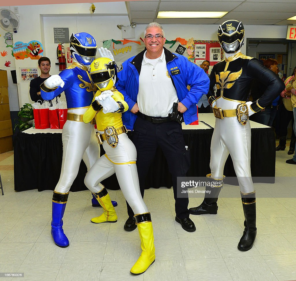 The Power Rangers pose with a NYPD officer at HELP Bronx Morris Avenue on November 20, 2012 in New York City.