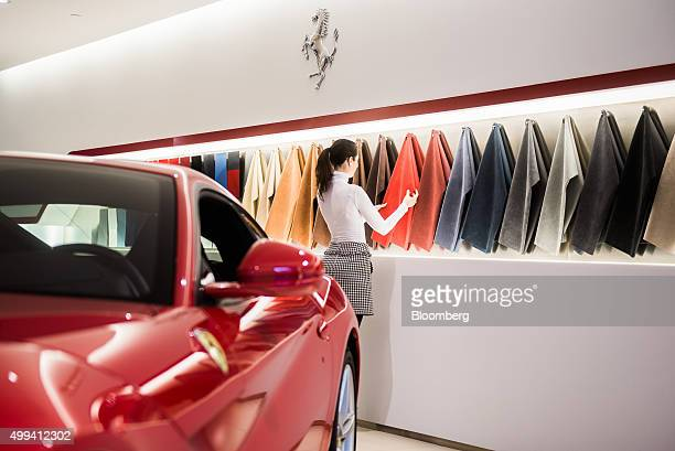 The prancing horse logo sits above an upholstery finish display as an employee arranges fabrics inside a Ferrari SpA dealership in Budapest Hungary...