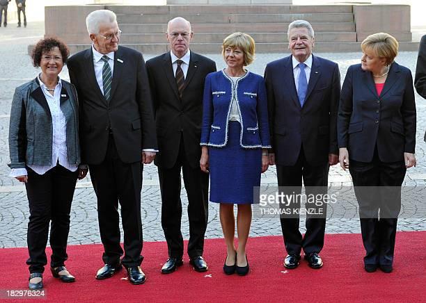 The premier of BadenWuerttemberg Winfried Kretschmann and his wife Gerlinde Kretschman stand next to Norbert Lammert president of the Bundestag...