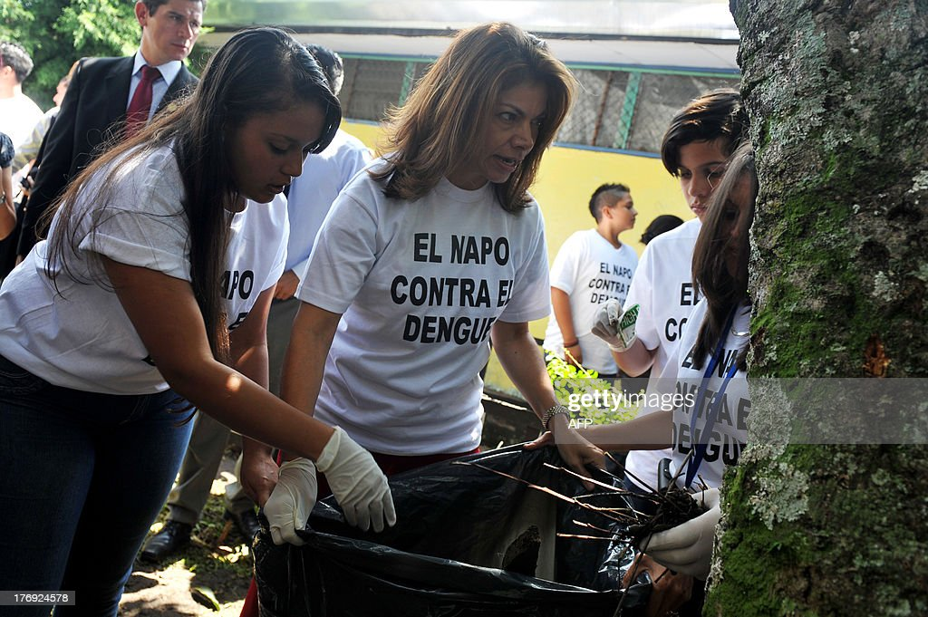 The President of Costa Rica, Laura Chinchilla (C), helps students of the Napoleon Quesada secondary school clear the school yard to eliminate possible breeding sources for the Aedes aegypti mosquito that carries the virus which causes dengue, as part of the 'National Educational Crusade Against Dengue', in San Jose, on August 19, 2013. An unusually potent outbreak of dengue fever had killed at least 26 people and infected nearly 40,000 more in 2013 by July in Central America, where the mosquito-born illness is endemic. The t-shirts read 'The Napo (Napoleon Quesada secondary school) Against Dengue'. AFP PHOTO/Hector RETAMAL