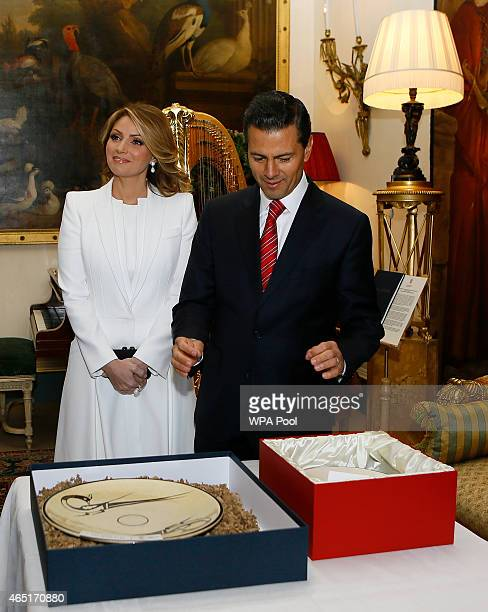 The President of Mexico Enrique Pena Nieto and first lady Angelica Rivera look at gifts given to them by Prince Charles Prince of Wales during a...