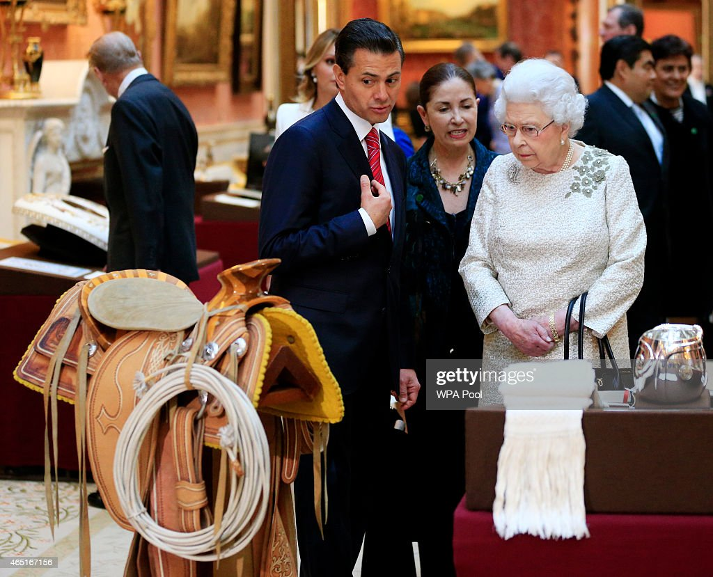 The President of Mexico Enrique Pena Nieto (centre) is shown Mexican items in the Royal Collection by Queen Elizabeth II at Buckingham Palace on March 3, 2015 in London, England. The President of Mexico, accompanied by Senora Angelica Rivera de Pena, are on a State Visit to the United Kingdom as the guests of Her Majesty The Queen from Tuesday 3rd March to Thursday 5th March.