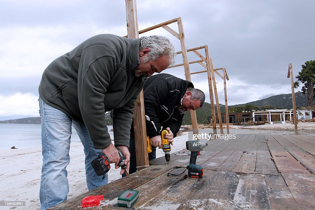 The president of the beach huts protection group and owner of the 'Beach Hut of the Silver Beach' restaurant, Ange Istria (L) symbolically demolishes on January 13, 2013 parts of his beach hut in front of the press in Porticcio. The South Corsica prefecture has ordered beach hut owners to demolish the parts that are located on the public property before January 15. If not respected the prefecture will conduct the demolition itself.