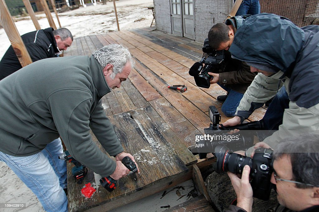 The president of the beach huts protection group and owner of the 'Beach Hut of the Silver Beach' restaurant, Ange Istria (2ndL) symbolically demolishes on January 13, 2013 a part of his beach hut in front of the press in Porticcio. The South Corsica prefecture has ordered beach hut owners to demolish the parts that are located on the public property before January 15. If not respected the prefecture will conduct the demolition itself.