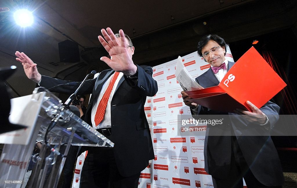 The President of the Belgian PS, winner of the elections in Belgium Elio Di Rupo (R) reads his documents before a press conference on the challenges facing Europe and Belgium with the Party of European Socialists (PES) President Poul Nyrup Rasmussen (L) in Brussels on June 16, 2010.